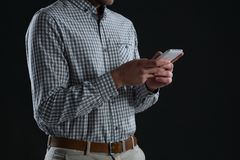Mid-section of man using mobile phone. Against black background Stock Photos