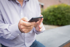 Mid section of a man using mobile phone Stock Photo