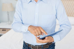 Mid section of man using tablet. In bedroom Stock Images