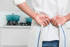 Mid section of man wearing apron in the kitchen Stock Photo