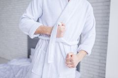 Mid section of man wearing bathrobe. At home stock photography