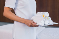 Mid section of masseur holding rolled up towels Royalty Free Stock Photography