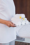 Mid section of masseur holding rolled up towels Royalty Free Stock Images