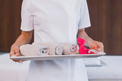 Mid section of masseur holding rolled up towels Stock Image