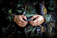 Mid section of military soldier using mobile phone in boot camp. War. Historical re-enactment with a soldier and an anachronistic cell smartphone to text stock image