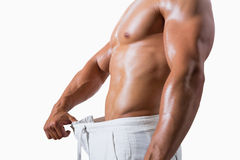 Mid section of a muscular man in an over sized pants Royalty Free Stock Images