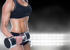 Mid-section of muscular woman lifting dumbell against bright light stock image