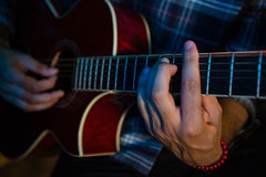 Mid section of musician playing guitar on stage Royalty Free Stock Photography