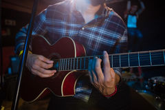Mid section of musician playing guitar on stage Stock Image