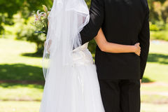 Mid section of a newlywed with arms around in park Stock Images