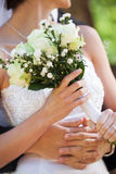 Mid section of a newlywed couple with bouquet in park Royalty Free Stock Photos
