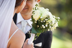 Mid section of a newlywed couple with bouquet in park Stock Image