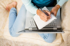 Free Mid Section Of Woman Writing On Notepad With Laptop On Her Legs Royalty Free Stock Images - 65333669