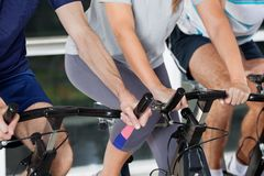 Mid Section Of People On Exercise Bikes Stock Image