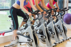 Mid section of people working out at spinning class. Mid section of four people working out at spinning class in gym Stock Photography