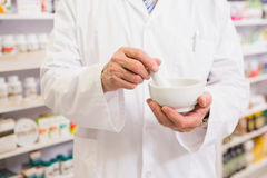 Mid section of pharmacist mixing medicine Stock Image