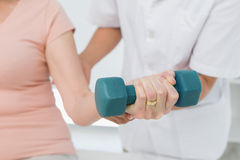 Mid section of physiotherapist assisting woman to lift dumbbell Stock Image