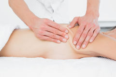 Mid section of a physiotherapist massaging womans body. Closeup mid section of a male physiotherapist massaging womans body in the medical office Royalty Free Stock Image