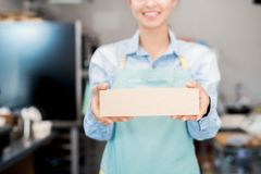 Takeaway Food. Mid section portrait of unrecognizable woman wearing apron holding box with takeaway food and smiling happily stock image