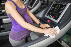 Mid section of pregnant woman cleaning treadmill. At the gym Stock Image