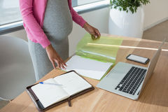 Mid section of pregnant woman working at desk Stock Photos