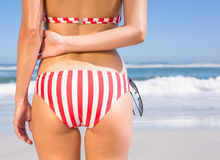 Mid section rear view of fit woman in bikini on the beach Royalty Free Stock Images