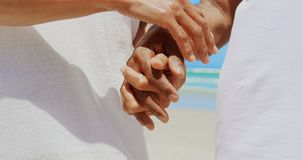 Mid section of romantic active senior African American couple holding hands on the beach 4k stock video footage