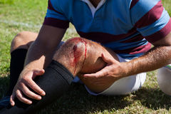 Mid section of rugby player with injured knee. Sitting on field Stock Photography
