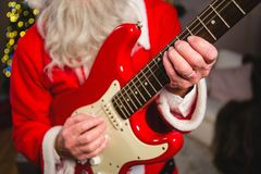 Mid-section of santa claus playing a guitar Stock Images