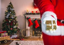 Mid section of santa holding christmas gift in living room Stock Photo