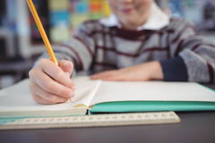 Mid section of schoolboy studying while sitting at desk. In classroom Stock Image