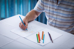 Mid section of senior man drawing in drawing book Stock Photography