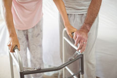 Mid section of senior man helping woman to walk with walker Royalty Free Stock Image