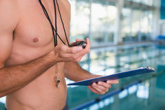Mid section of shirtless coach with stopwatch by pool at leisure center Royalty Free Stock Image