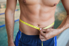 Mid section of shirtless fit swimmer measuring waist by pool Royalty Free Stock Photo