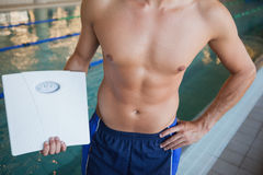 Mid section of a shirtless fit swimmer with weighing scales by pool Royalty Free Stock Photo