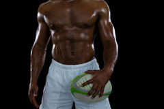 Mid section of shirtless male athlete holding rugby ball Royalty Free Stock Images