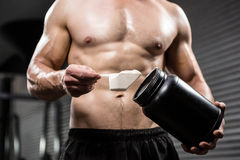 Mid section of shirtless man taking proteins from can. At the crossfit gym Stock Photo