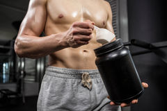 Mid section of shirtless man taking proteins from can. At the crossfit gym Stock Photos