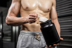 Mid section of shirtless man taking proteins from can Stock Photo