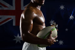 Mid section of shirtless man with trophy and rugby ball against Australian flag Royalty Free Stock Images