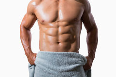 Mid section of a shirtless muscular man wrapped in towel Stock Images