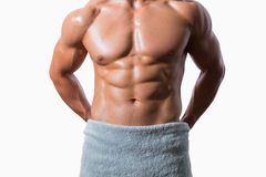 Mid section of a shirtless muscular man wrapped in white towel Royalty Free Stock Photo