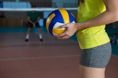 Mid section side view of volleyball player holding ball. Mid section side view of female volleyball player holding ball at court Stock Photography
