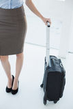 Mid section on slender classy businesswoman holding a suitcase Royalty Free Stock Image