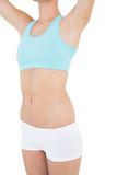 Mid section of slim woman wearing sportswear lifting her arms Royalty Free Stock Image