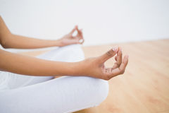 Mid section of slim young woman meditating sitting in lotus position Royalty Free Stock Photo