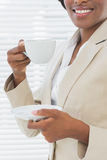 Mid section of smiling businesswoman with a cup of tea Royalty Free Stock Images