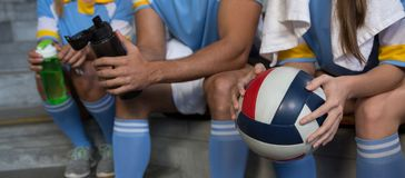 Mid section of sports team holding volleyball Royalty Free Stock Image