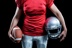Mid section of sportsman holding American football and helmet Stock Photos